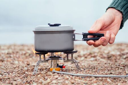 The pan with the porridge stands on the gas burner Camping Stove . On the background of the river