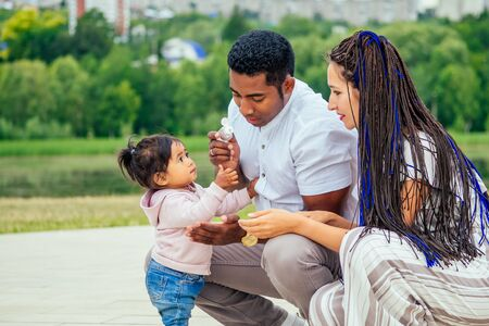 happy family applying hand-sanitizer anti-bacterial gel to daughter hands