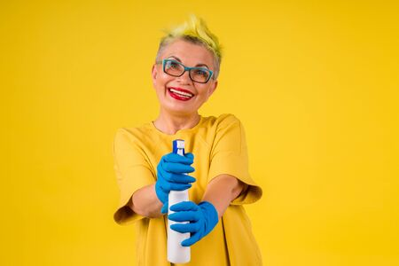 mature woman with colored stylish yellow dyed hair in warm dress washing floor at home background studio copy spase Zdjęcie Seryjne