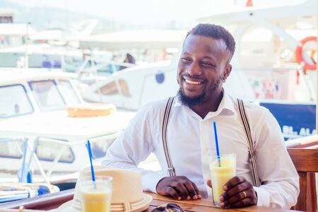 handsome african american business man with healthy smoothie in summer beach tropical cafe in Turkey
