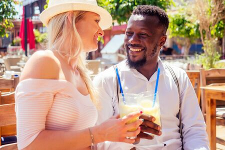 african american man and a woman look lovingly at each in summer tropical cafe and drinking fresh fruit orange cocktail