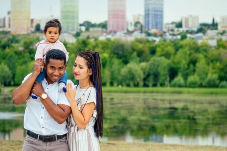 transnational interracial mother and father walking with their mixed race baby girl in autumn park