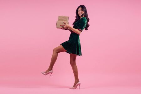 full height Portrait of beautiful fashion curls hairstyle brunette model in silk velvet green dress holding New Years and Christmas boxes with gifts on a pink background in the studio