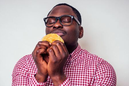 Illness sad african american man put hand on pain abdomen of hamburger.handsome and young afro man in a stylish shirt and glasses holding a burger on a white background. junk food diet indigestion Stock Photo