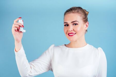 woman in a white blouse holds an inhaler on a blue background