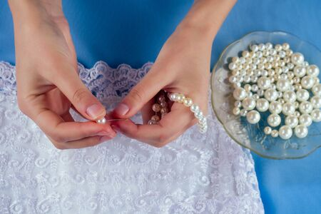 close-up hands of woman seamstress tailor dressmaker designer wedding dress sews pearl beads to lace on a blue background in the studio Stok Fotoğraf