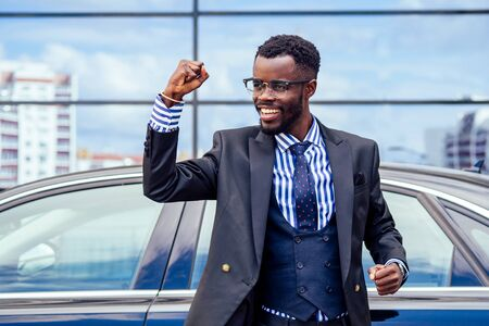 happy and successful afro american businessman rejoices and enjoying success ahead of the car. concept of a good deal and victory