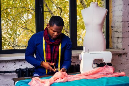 portrait of a handsome african man smiling seamstress with sewing machine.Afrio American man stylish designer working in tailor workshop mannequin,table measuring tape in room against autumn window Banco de Imagens