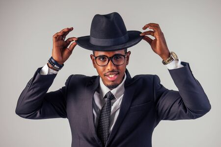 Retro style well dressed African american business man model in dark suit and black hat in studio on white background