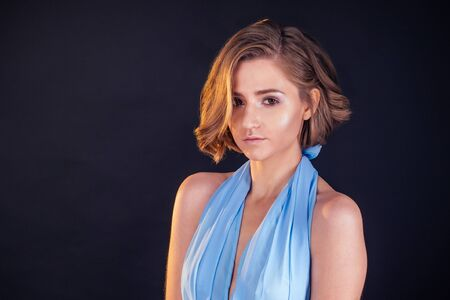 portrait of a young woman in windy blue dress. Beautiful girl with creative make-up and short haircut hairstyle
