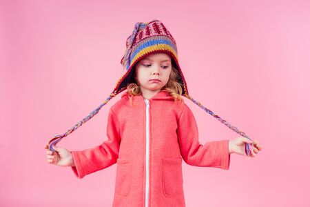 portrait of happy charming little girl wearing knitted funny hat from Himalayas Nepal on pink background in studio. Fashion autumn winter season sale concept tourist preparing to go to the mountains 版權商用圖片