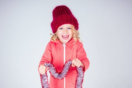 Beautiful little girl in dress and red knitted hat in studio on white background. Happy little smiling female child with shiny Christmas tinsel. Christmas miracles Happy New Year