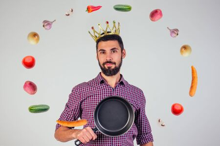 king of the kitchen with a golden crown on head chef holding a frying pan wizard man is cooking magic flying food salad, carrot, garlic, onion, pepper, potato, cucumber isolate white background studio