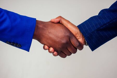 Portrait of two businessmen shaking hands in a business meeting on white background in studio shot Stok Fotoğraf