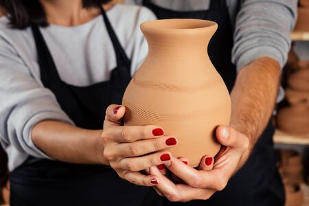 a pottery salesman and salewoman sells a clay vase pot close up in workshop