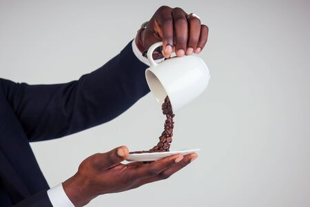 hands of afro american business man in a black classic suit holding a cup with flying coffee bean splash on plate in white background studio shot. Magic morning drink