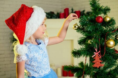Cute little child blonde curls hairstyle girl in red santa claus hat and dress decorating Christmas tree with toys baubles indoors Xmas morning. preparing home for xmas celebration New years night. Stock Photo