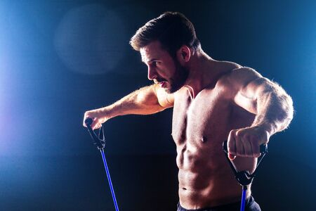 Muscular fitness man antique perfect muscles six pack abs and bare chest bodybuilder model exercising with stretching rubber stretching band on a black background in the studio training workout gym