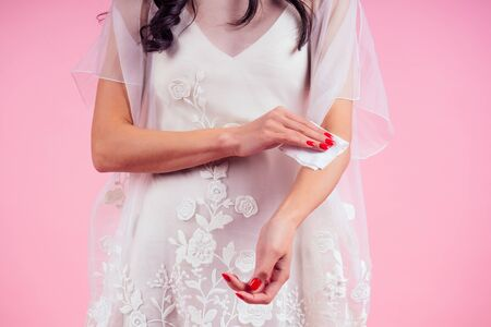 Woman bride in white dress part of the body of a young woman in a pink studio . girl using wet wipes the sweat hand applying hand sanitizer on a pink background in the studio.