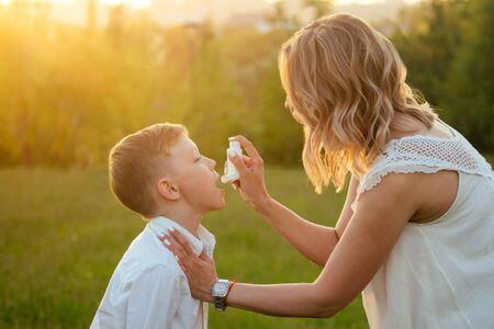 Fürsorgliche Mutter benutzt einen Inhalator für ihren Sohn im Park