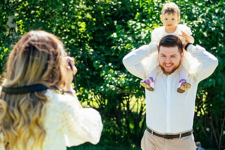 happy and stylish family in the summer park. family photosession woman photographer photographing bearded husband and cute daughter looking at camera Stok Fotoğraf