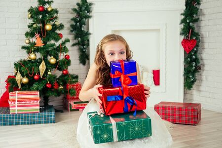 Cute little girl in a nice dress with long curly blond hair dreaming and holding a lot of gifts box at home near a Christmas tree with gifts and garlands and a decorated fireplace .new Year morning