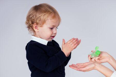 Retrato de un lindo niño rubio aplicando gel antiséptico antibacteriano en las manos contra virus bacterianos en estudio sobre fondo blanco. protección contra la epidemia del bebé, mano de las madres de primer plano