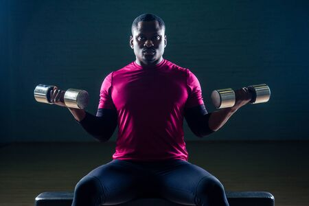 muscular african american man doing push-ups exercises with weights dumbbell in the gym on a black background Stock Photo