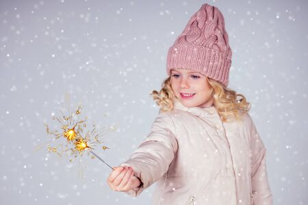 charming little girl in a knitted hat holding fireworks on white background in a studio.Cute blonde child with xmas dream.Happy kid enjoy the fire sparks. new year holidays eve of Christmas a wish