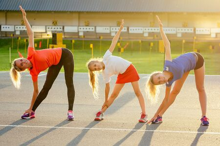 active family at outdoor. two blonde woman twin sisters and their daughters in stylish sportswear warm up and do exercises crossfit and fitness in the stadium . group of four girls in the park.