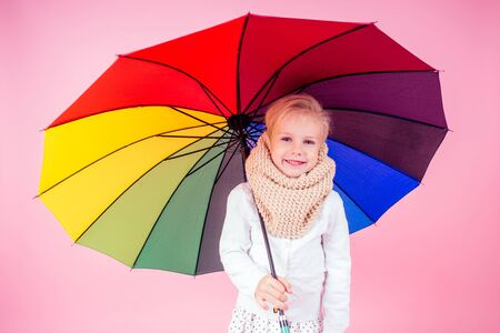 portrait of happy and beautiful little blonde girl blue eyes in beige knitted scarf holding a colorful rainbow umbrella autumnal springtime season in the studio on a pink background.charming child