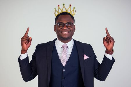 Confident businessman business king in a black classic suit with a tie and glasses put on a crown on head in white background in studio Imagens