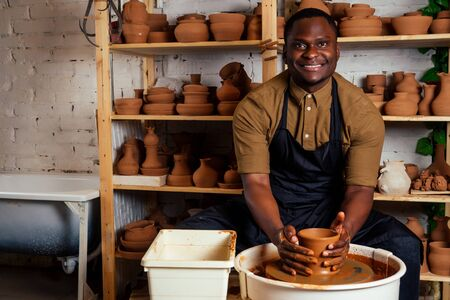 happy dark-skinned african american businessman potter man molding In workshop. sculptor pottering clay pot in a studio workplace. creativity and inspiration of the artist