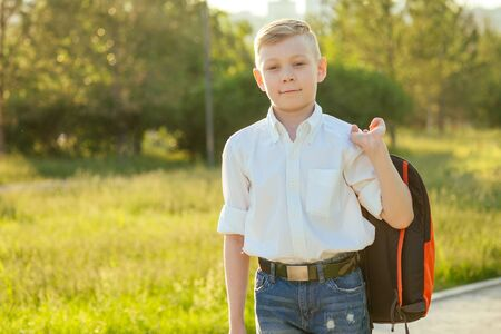 stylish and young schoolboy in a white shirt and jeans with a backpack in the park going to school Stock Photo