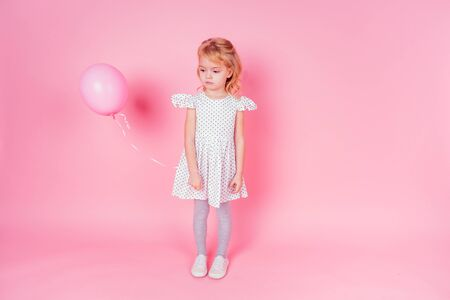 sad little blonde girl in white dress in peas 4-5 year old holding balloon in the studio on a pink background,birthday celebration ,sadness and disappointment sorrow
