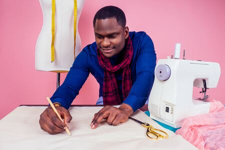 African American man tailor seamstress workshop stylish male model clothes designer the process of creating a new collection of dresses on pink background in the studio copyspace
