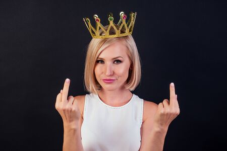 business woman blonde with a golden crown on her head showing fuck off with the middle finger studio shot black background