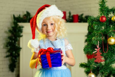 Close-up portrait of a blonde curls little girl in santa hat with a gift dreaming about christmas miracles standing next to the christmas tree and fireplace bright interior of the house