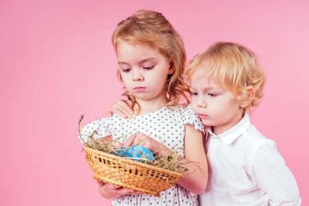 two little blonde child with a chick cock easter in studio pink background.beautiful boy and girl kids celebrating Easter Holiday with pets, painted eggs in wicker basket.dream birthday present