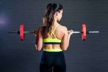young woman in green sports bra and black pants doing exercises with red barbell on black bricks background. Zdjęcie Seryjne