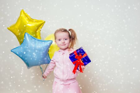 cute little girl holding helium blue, yellow and gold balloons and a box with a gift happy Birthday on white background in studio .christmas and new year holiday