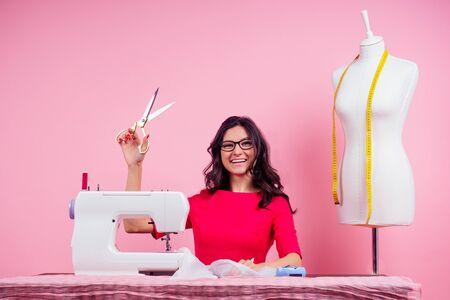 Schnittmuster, Nähmaschine und Puppe im Studio rosa background.seamstress Curve Template. Schneider erstellt eine Kollektion Outfits näht Kleidung in der Werkstatt. Designerkleidung für junge Frau Notizen Ideen