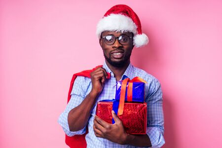 African American man wearing stylish plaid shirt great smile in santa hat with gift box on pink background studio.dark-skinned Santa Claus merry christmas with sack full of Christmas goodies Stock Photo