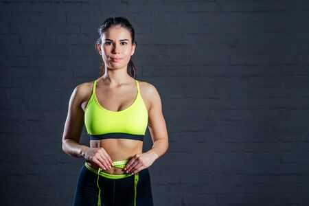 beautiful young girl in green sports bra with measuring tape. Diet, weight loss - concept