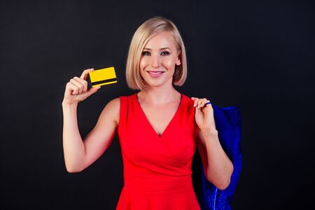 attractive blond woman in red dress holds a leather blue bag in high heels full-length studio shot in black background. black Friday shopping sale concept Reklamní fotografie