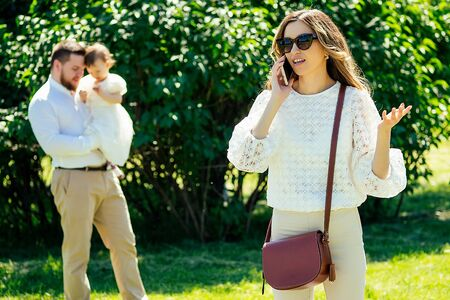 rich and beautiful woman cagy stylish sunglasses talking on the phone with her lover paramour on the phone in the park behind husband and daughter . the concept of divorce and adultery