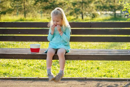 cute little blonde girl daughter eating french fries sitting on a bench in the park . unhealthy food in childhood 写真素材