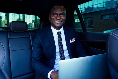 Handsome successful rich african american business men entrepreneur in a stylish black suit and tie sitting in a luxury car and works with laptop business partner online conference Foto de archivo
