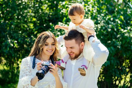 happy and stylish family in the summer park. family photosession woman photographer photographing bearded husband and cute daughter looking watching photos at camera