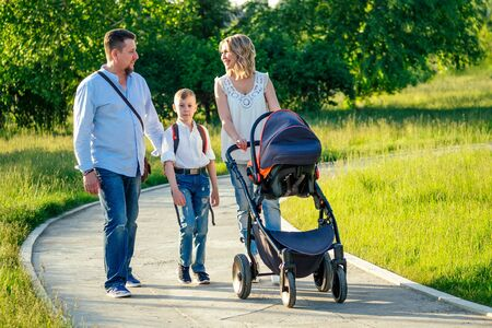 active big family father, mother, son and baby in stroller walking in the park
